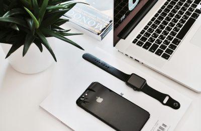 Schreibtischoberfläche mit macbook, Handy und Uhr