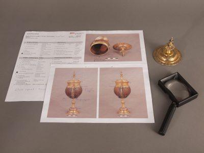 Anhand eines Protokolls und mit Hilfe einer Lupe wird der Zustand der Objekte überprüft und festgehalten.