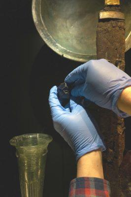 Restaurator Martin Raithelhuber entnimmt eine sogenannte Schwertperle aus einer Vitrine der Schausammlungen.