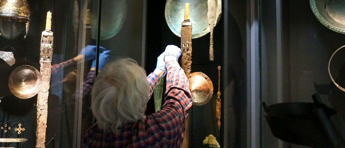 Restaurator Martin Raithelhuber entnimmt ein Objekt aus einer Vitrine der Schausammlung.