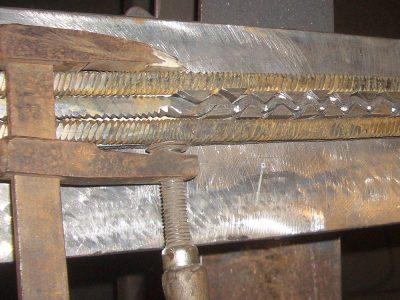 Die Herausforderung beim Nachschmieden des Schlangen-Schwertes von Hemmingen bestand darin, dass die Füllstücke der Schlangen-Windungen einzeln hergestellt waren und durch die Hammerschläge beim Feuerverschweißen leicht hätten herausspringen können. Steven Spranger löste das Problem, indem er die Füllungen zum Klingenkern hin breiter formte und sie sich dadurch in den Hinterschneidungen des Schlangenmotivs und der gedrehten Stahlstäbe verkeilten. Zum Anpassen der Füllstücke fixierte er die Teile der Schlangenseite des Musterstreifens mit einer Schraubzwinge. © Axon der Schmied, Foto: Steven Spranger, CC BY-SA