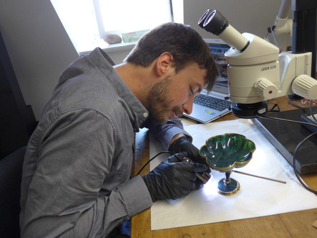 Stefan Hanß beim Objektstudium einer Fußschale aus Nephrit mit Mikroskop