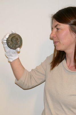 Eine Frau mit einer großen römischen Münze in der Hand